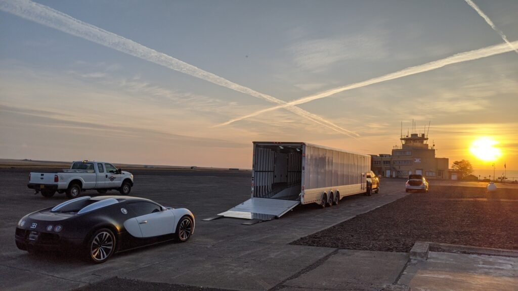Sun setting just to the right of an air traffic control tower, with a black and white Bugatti getting loaded onto an enclosed trailer in white