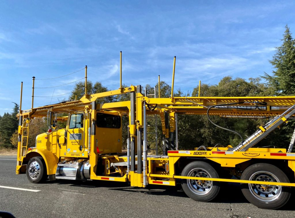 auto transport yellow semi truck with an empty yellow open car trailer driving from right to left on a right sunny day